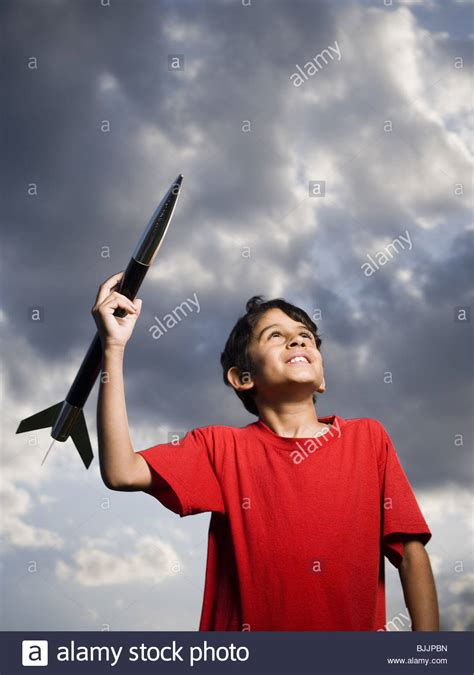 Boy playing with toy rocket outdoors on cloudy day low